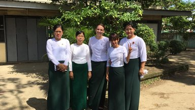 Five women teachers dressed in long green skirts and white shirts, standing outside of the school.