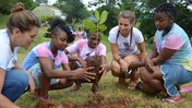 Two Peace Corps Volunteers and three Jamaican teens crouch down in a semi-circle as they plant a tree during Camp GLOW.