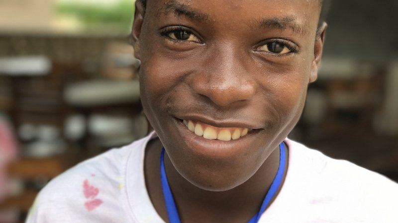 "A Togolese boy smiling wearing ""Camp Joie"" t-shirt."
