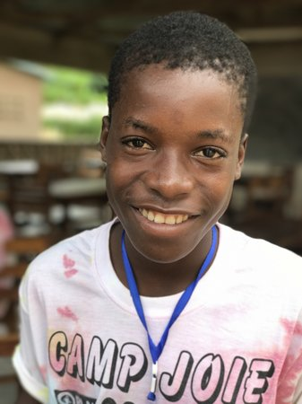 """A Togolese boy smiling wearing """"Camp Joie"""" t-shirt."""