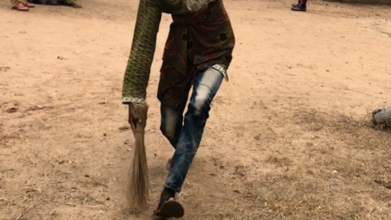 A Togolese girl running with a bucket on her head and a traditional broom in her hand.