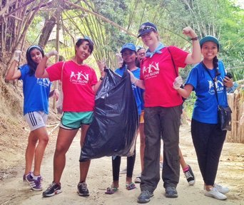 """Counselors and campers take a minute for a """"strong women"""" pose during the trash clean up."""