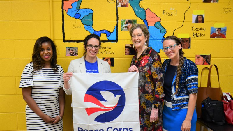Four women stand together in a classroom holding a Peace Corps flag.