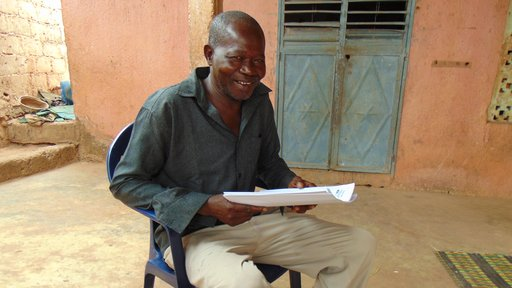 Mahamadou Coulibaly, a Senegalese national and Peace Corps counterpart, sit on a chair outside holding a report.