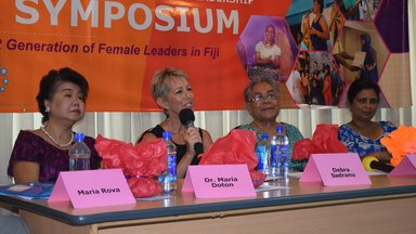 This photo shows the four leaders from the Women's Symposium with a table and name tags.