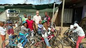 Dave Gorman and Tumi Taabe pose with kids on bikes