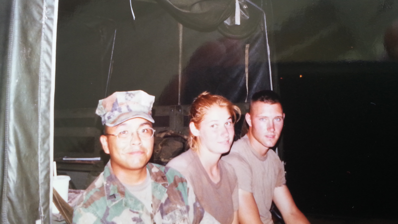 An American female Marine smiles while sitting on the back of a truck with a fellow American and a Thai national in army fatigues.