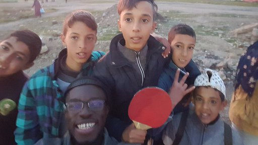 A black, male Volunteer smiles for a selfie outside with many Moroccan children