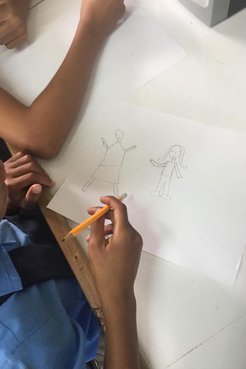 Up close shot of Jamaican student drawing with yellow pencil in a white classroom