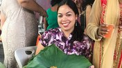 Volunteer sitting displaying seven curry in lily leaf at local wedding