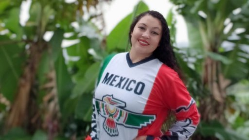 Female Mexican American Peace Corps Volunteer poses in green foliage of Jamaica in Mexican National Football Team Jersey