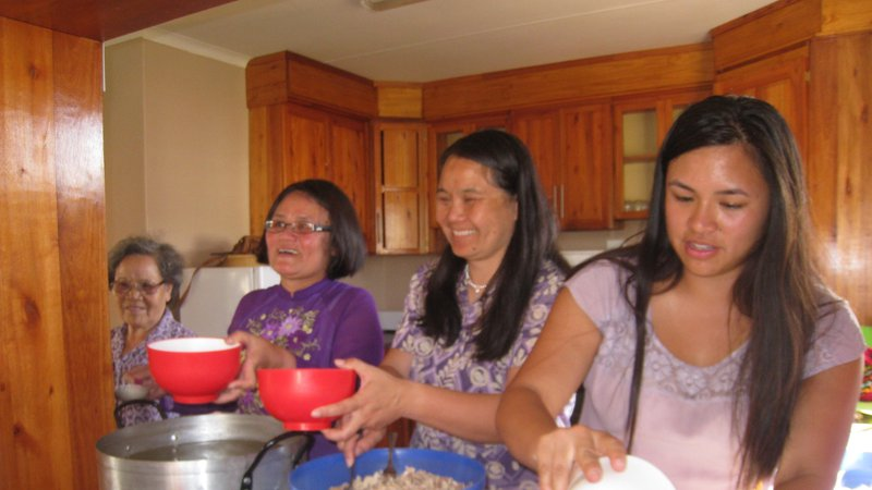 Four Asian American women stand side by side in a kitchen. They are cooking together.