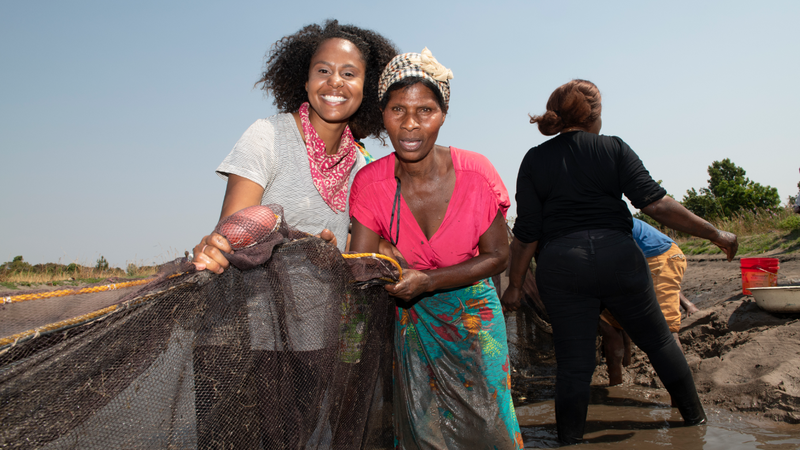 An African-American Peace Corps Volunteer (left) stands with a Zambian woman. They are holding a large fishing net.