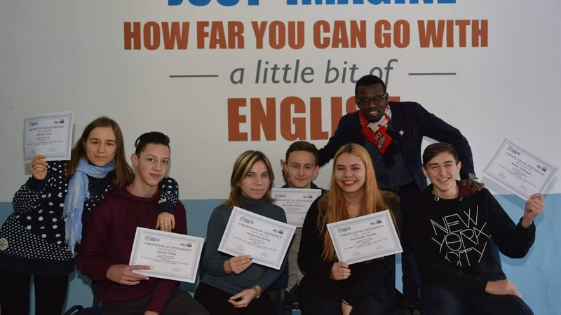 Volunteer Fabenson Frisch poses with six locals. They're smiling and holding certificates of English Camp completion.