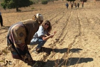"""Peace Corps Volunteer Chelsea Rinnig works with a community member to make lines with a """"ripper,"""" a tool that assists in the strip plowing process."""