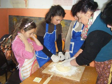 A local woman instucts young girls on proper culinary practices