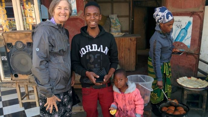 A white woman stands with her Tanzanian friend and a child, smiling.