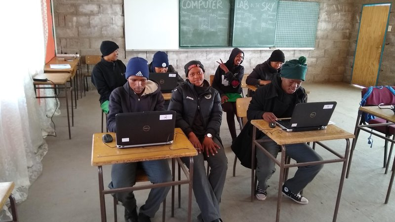 Seven African students work at computers in a classroom in Lesotho