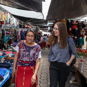 A female Peace Corps Volunteer walks with a Guatemalan counterpart through a busy open air market.