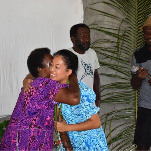 An Asian American Peace Corps Volunteer hugs a counterpart in Vanuatu. They are dressed in colorful clothing.