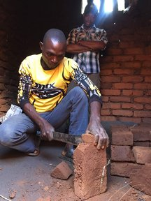 Volunteer Justin observes a cookstove being built