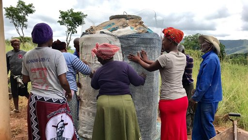 Community members securing  concrete tank, so that it may dry.