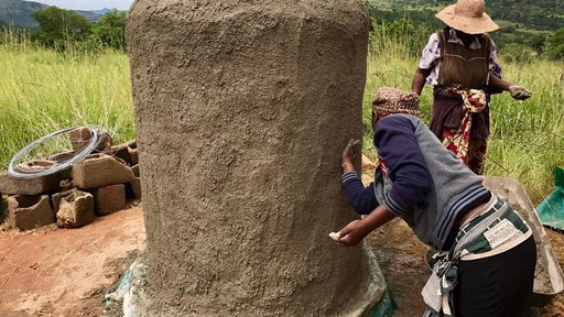 Women spreading cement to make the structure.
