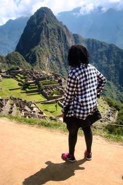 A Peace Corps Volunteer stands with her back to the camera. Machu Picchu, a bold mountain peak, is in the background.