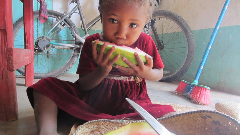A young girl in Madagascar sits on the floor eating a large chunk of watermelon.