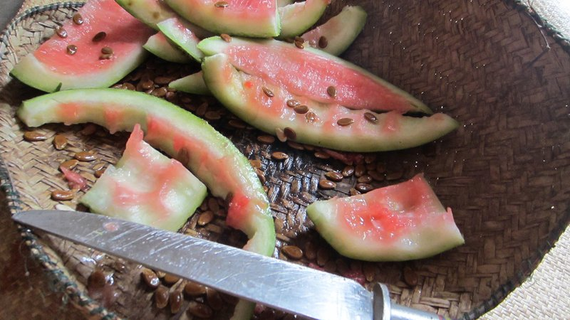 Watermelon rinds and seeds sit alongside a knife on a woven mat.