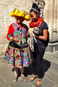 A Peace Corps Volunteer stands next to a woman in traditional Peruvian dress. The Volunteer is holding a baby sheep in her ar