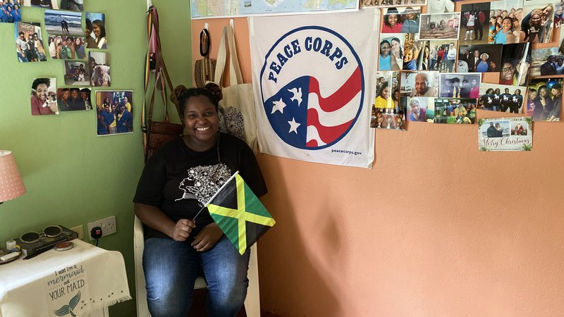 A young, black female smiles in her home in front of a Jamaican flag and a Peace Corps flag.