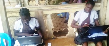 The girls coding at a farming store which provided them with a generator because power was out.