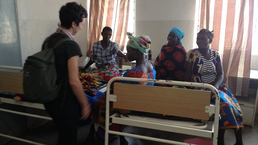 American friend of Volunteer greets Malawian women sitting on a bed in a health center