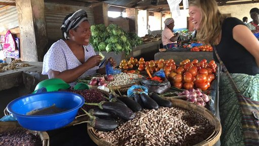 Volunteer Katlyn leans over a table of vegetables smiling to chat with a Malawian women selling them