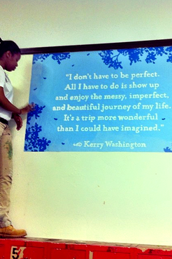 """Brittany stands to the left of the frame on top of a cabinet. She is beside a freshly painted mural with a quote from Kerry Washington that reads, """"I don't have to be perfect. All I have to do is show up and enjoy the messy, imperfect and beautiful journey of my life. It's a trip more wonderful than I could have imagined."""""""