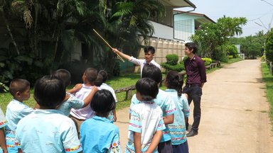 Students standing outside getting instructions from the teacher.