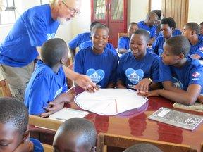 Volunteer David helps girls design on a healthy plateIMG_4478.JPG