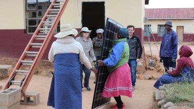Women of the Community Lifting Solar Panel