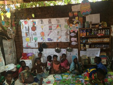 A nursery school classroom transformed using lessons learned from the Perivoli Schools Trust approach. Previously, this classroom was an empty thatch shack. Now, it's filled with activities and learning aids aimed at young children.