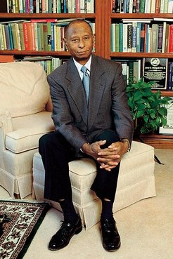 A older African American man in a suit sits in a home library.