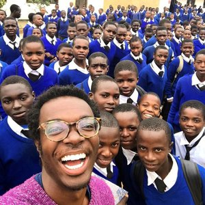 A young black man wearing round tortoise glasses takes a selfie with a group of Tanzanian students. The students are dressed