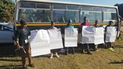 A Peace Corps volunteer stands with South African community members outside in front of a bus. There are flip chart papers ta
