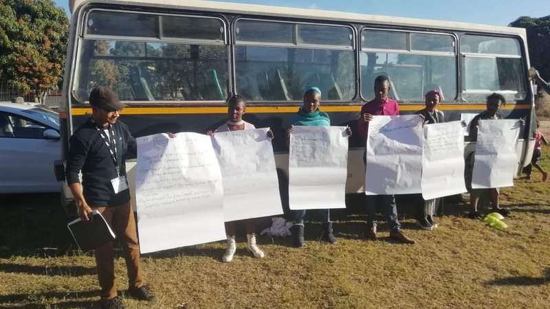 A Peace Corps volunteer stands with South African community members outside in front of a bus. There are flip chart papers taped to the side of the bus.