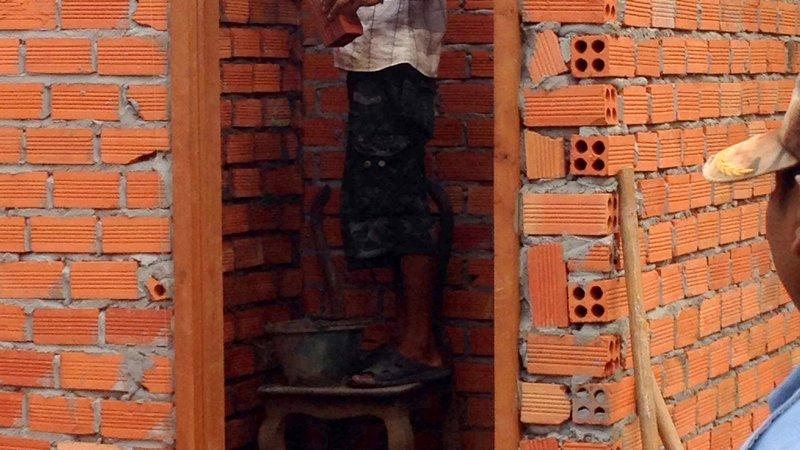 Cambodia: A community member lays bricks for the new latrines.