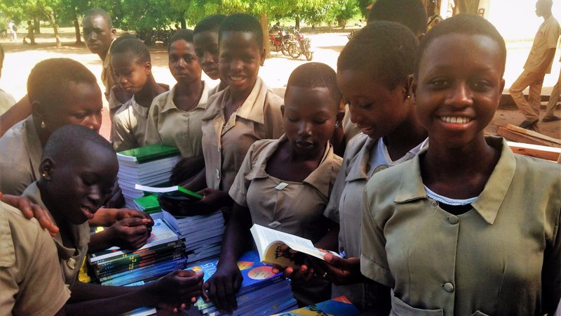"Girls receiving books from the ""Books for Benin"" project."