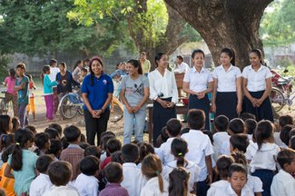 A female Peace Corps Volunteer and many adolescent girls stand outside in front of a crowd.