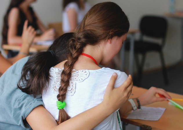 Two girls sit in a classroom, one hugs the other.