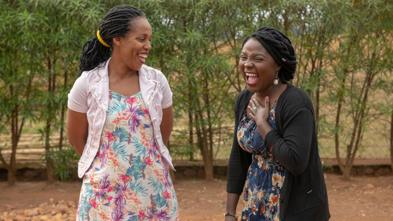 Two black women stand beside each other, smiling and laughing.