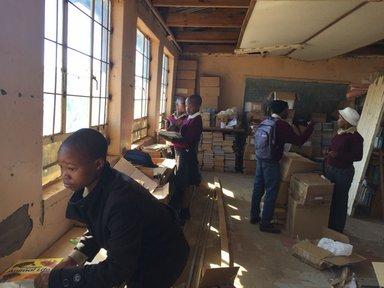 School children are standing in the current school multipurpose room.
